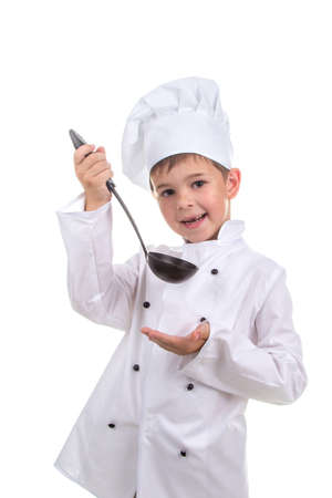 Beautiful smiling little boy in chefs hat with ladle tastes the cooked broth.