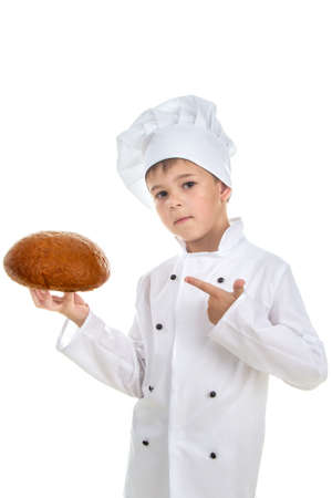 breaking: Cute boy chef demonstrates delicious fresh bread, isolated on white background