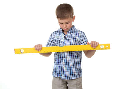 a cute thoughtful builder assistant in a blue checkered shirt holds a big yellow construction ruler