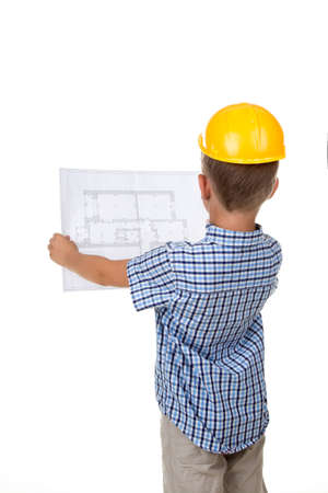 Young serious builder reading a construction plan, turned back, isolated on white Stock Photo