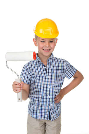 Cute little boy in yellow hardhat and blue checkered shirt playing a painter, isolated on white background Stock Photo
