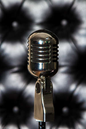 Vintage microphone on the luxury, black leather background.