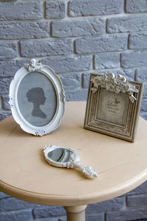 Old picture frames, lying mirror on the table with grey brick wall background, remote view.