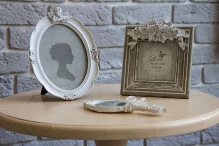 Old picture frames, lying mirror on the table with grey brick wall background, closeup.