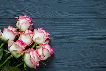 A bouquet of pink roses, on the navy rustic wooden table