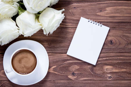 Bouquet of roses, notebook and coffee cup on wooden table, top view