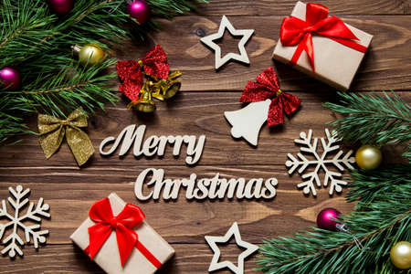 Merry Christmas decoration with bell, gifts, snowflakes, stars and other tinsel on the wooden background Stock Photo