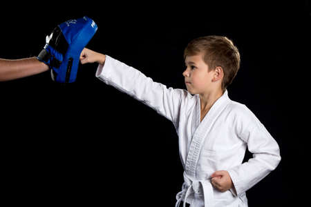 Karate training, straight hit with clenched fist to the blue punching pad Stock Photo