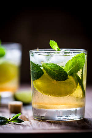 Extremely nice composition of Mojito half glass with mint and lime on the wooden table. Blurred background. Front view Stock Photo