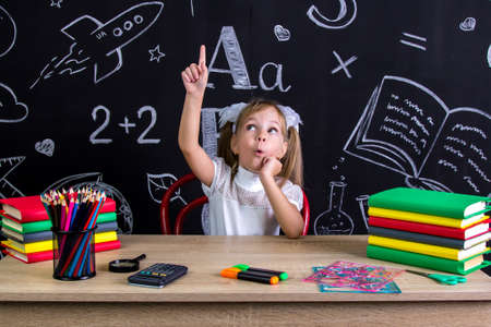 Excited schoolgirl sitting at the desk with books, school supplies, holding her right pointing finger up, with a surprisingly opened mouth
