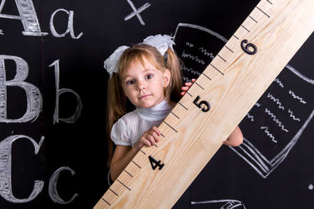 Cute schoolgirl standing before the chalkboard as a background holding the huge ruler diagonally Foto de archivo