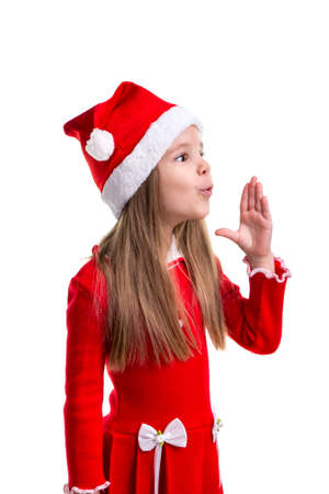 Miracle christmas girl blowing the air with raised hand, wearing a santa hat isolated over a white background