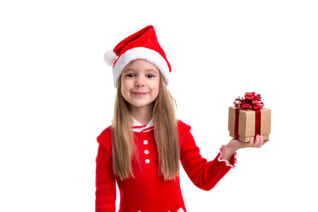 Happy christmas girl holding a gift it in the left hand, wearing a santa hat isolated over a white background