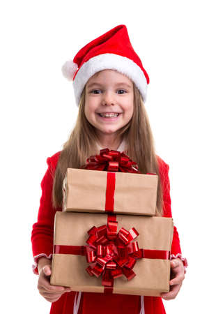 Cheered and happy christmas girl holding two gift boxes in the hands, wearing a santa hat isolated over a white background