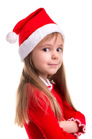 Smiling coquettish christmas girl wearing a santa hat isolated over a white background, standing in the half turn. Portrait picture, closeup
