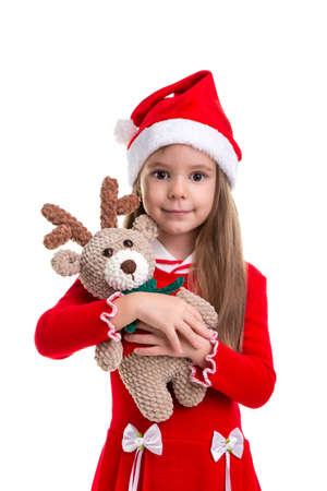 Christmas girl hugging the deer soft toy, wearing a santa hat isolated over a white background