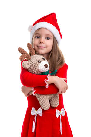 Lovely christmas girl hugging the deer soft toy, wearing a santa hat isolated over a white background