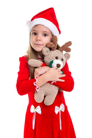 Happy beautiful christmas girl hugging the deer soft toy, wearing a santa hat isolated over a white background Imagens