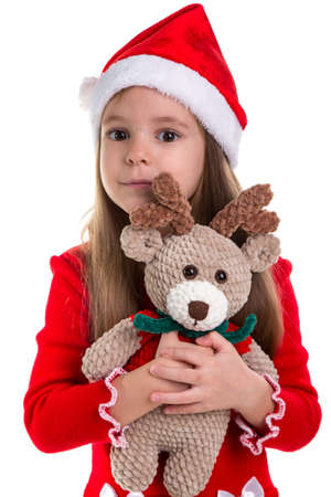 Girl huggs the deer soft toy, wearing a santa costume isolated over a white background