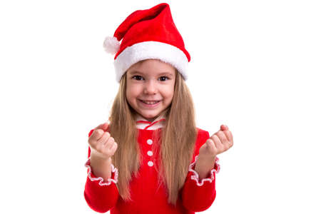 Christmas girl clenching the fists, wearing a santa costume, isolated over a white background Imagens
