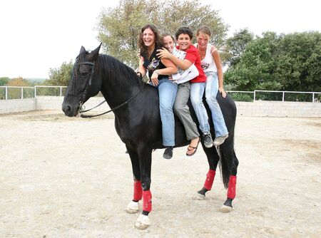 pony girl: happy teenagers and black horse
