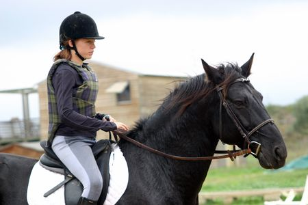 riding: black horse and girl Stock Photo