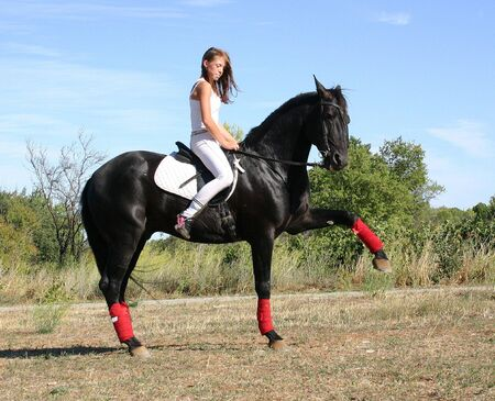 pony girl: riding woman and her black stallion