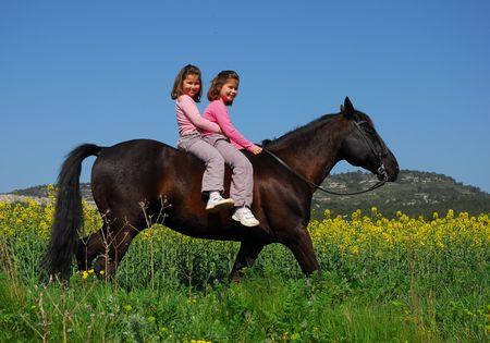 niñas gemelas: Equitación gemelos  Foto de archivo