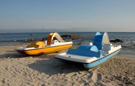 corse: two blue and yellow pedallos on a beach of corse  Stock Photo