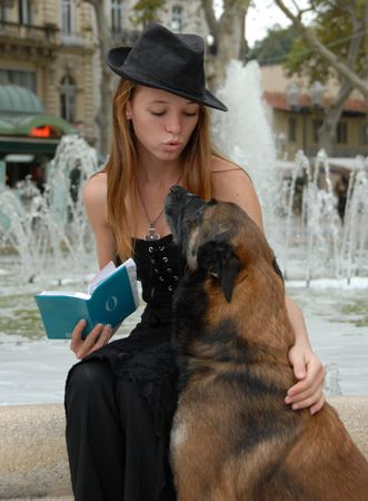 beautiful teenager reading her book with her dog