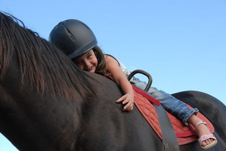 pony girl: very young little girl on her black stallion Stock Photo