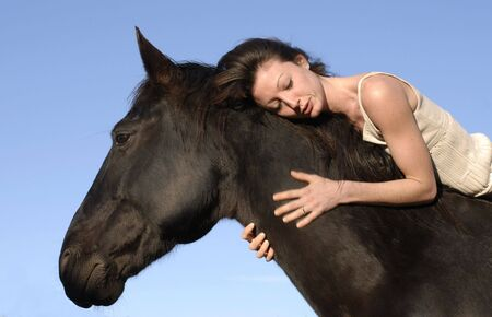 horse laugh: young woman and her best friend black stallion