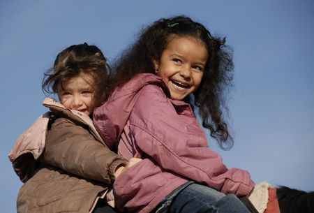 diverse: two laughing little girls on a horse : the best friends