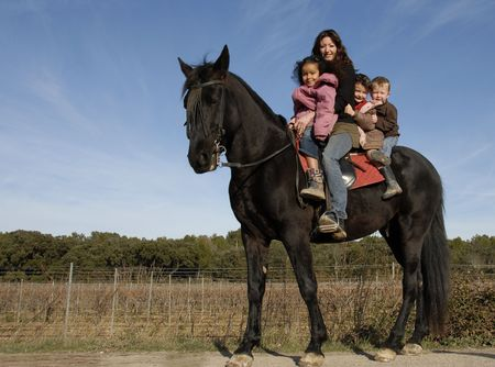 metis: children and mother and a black stallion on a street