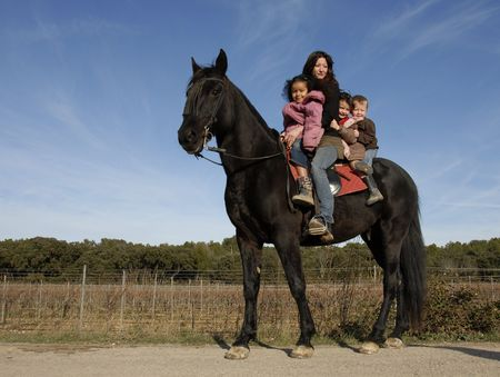 children and mother and a black stallion on a street photo