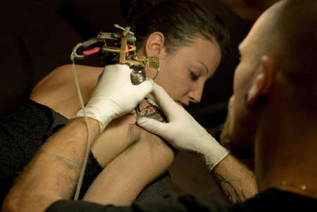 an young tattoo artist  tattooing a woman with a professionnal stylet