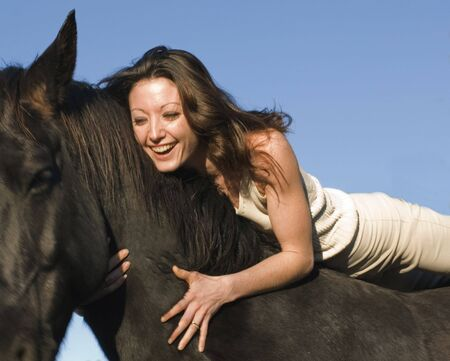 horse laugh: happy young woman and her best friend black stallion