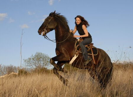 rearing: rearing dangerous stallion and young woman in a field