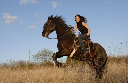 rearing black stallion and happy young woman in a field photo