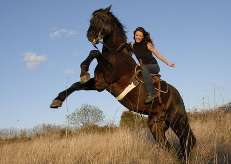 horse laugh: rearing black stallion and happy young woman in a field