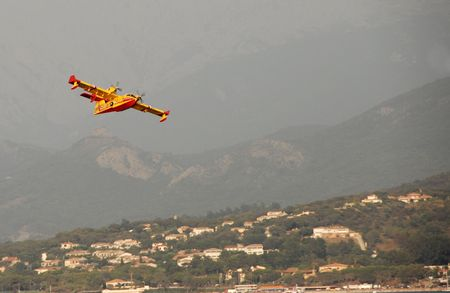 Canadair in aproach to stop forest fires near houses photo