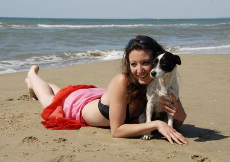 happy young woman on the beach with her little dog photo