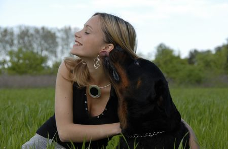 laughing young woman and her purebred rottweiler