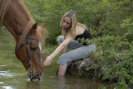 caballo bebe: joven adolescente con su semental marr�n de un r�o (se centran en la mujer)