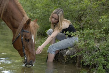 horse blonde: young teenager with her brown stallion in a river (focus on the woman) Stock Photo