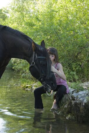 rein: young teenager are kissing her black horse in a river