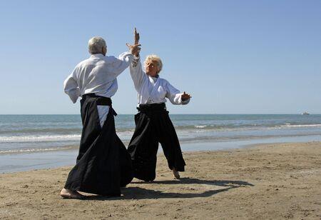 Deux adultes sont en formation Aïkido sur la plage  Banque d'images - 2997088