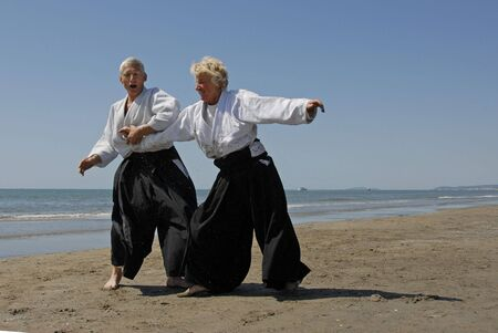 adherent: Two adults seniors are training in Aikido on the beach