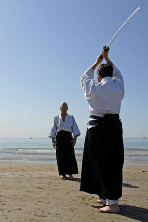 adherent: Two adults are training in Aikido on the beach