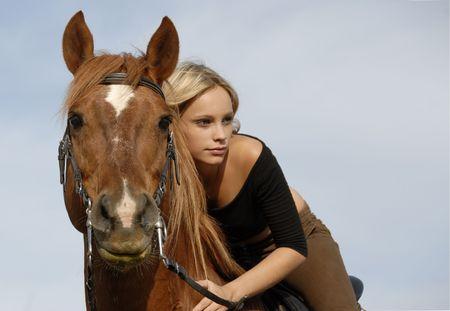 femme a cheval: blonde adolescente et son cheval brun en bleu ciel